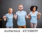 happy volunteers in blue t... | Shutterstock . vector #657338059