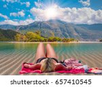 woman sunbathing on beach  | Shutterstock . vector #657410545