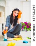 Small photo of Young weary housewife sits on the floor at home with cleaners for cleaning