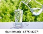 overflowing water in a glass... | Shutterstock . vector #657548377
