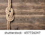 rope knot on wooden board | Shutterstock . vector #657726247