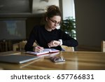 Small photo of Talented female writer in stylish eyeglasses noting some information in notepad while looking on alarm watch to managing time for organization of working process sitting in university indoors