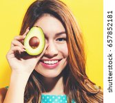 Small photo of Happy young woman holding an avocado halve on a yellow background