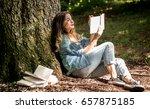 girl reading a book near a tree ... | Shutterstock . vector #657875185