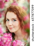 Small photo of The girl's portrait with blue eyes in the blossoming apple-tree with claret flowers