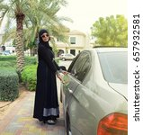 Small photo of Getting ready. Portrait of young arabic smiling lady standing near car and opening door. wearing abaya and hijab.