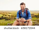 man sits on the rock using... | Shutterstock . vector #658172044