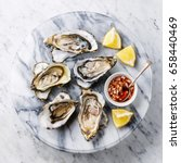 open shucked oysters with lemon ... | Shutterstock . vector #658440469