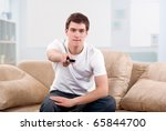 Man changing TV channels with remote control sitting on sofa at home - stock photo