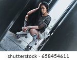 Small photo of She is all about fashion. Attractive young woman in rollers keeping hand in hair while crouching outdoors