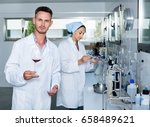 Small photo of Young man in white coat checking wine acidity and sugar saturation in chemical laboratory at a winery