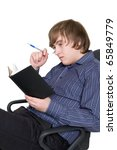 young man with with pen and notebook in a chair - stock photo