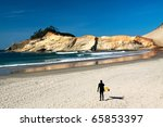 A lone surfer holds his surf board as he studies in the incoming waves in the ocean. - stock photo