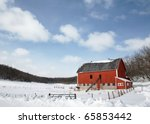 A red dairy barn in a very rural county scene in the middle of a snowy field. - stock photo