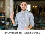 happy man with laptop showing a ... | Shutterstock . vector #658534459