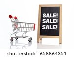 Small photo of Sale! Sale! Sale! Shopping cart and chalkboard on white background.