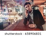 handsome businessman in bar is... | Shutterstock . vector #658906831