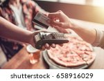 cropped image of men paying via ... | Shutterstock . vector #658916029