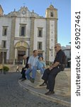 Small photo of Evora, Alentejo, Portugal, 26-September-2007: Four people sitting in front of a wonderfully majestic building in Evora.