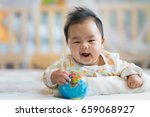 newborn boy smile on the bed... | Shutterstock . vector #659068927