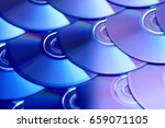 Small photo of Compact discs background. Several cd dvd blu-ray discs. Optical recordable or rewritable digital data storage.