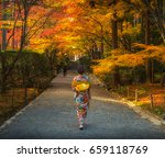 Small photo of Japanese woman walking with traditional kimono in autumn japan