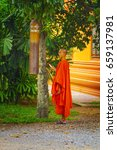 Small photo of WAT PREAH PROM RATH, CAMBODIA - JANUARY 6, 2016 - Buddhist monk ringing bell in Wat Preah Prom Rath complex.