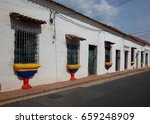 Small photo of A street in Mompox with windows painted in the colours of the Colombian flag