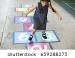 young girl playing hopscotch | Shutterstock . vector #659288275
