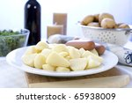 Peeled and cut potatoes, sausage and kale, ingredients for a Dutch stamppot. - stock photo