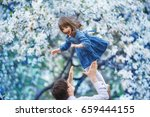 a man throws his daughter up... | Shutterstock . vector #659444155