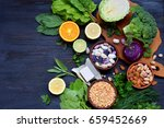 Small photo of Composition on a dark background of products containing folic acid, vitamin B9 - green leafy vegetables, citrus, beans, peas, nuts, yeast. Top view. Flat lay. Healthy food