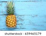 ripe pineapple on blue wooden...   Shutterstock . vector #659465179