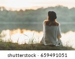 a girl sitting on the river... | Shutterstock . vector #659491051
