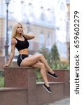 Small photo of Beautiful strong blonde tattooed girl sitting on the street outdoor at the evening in shorts and showing her perfect abdominal muscles.