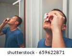 man with nose bleed in bathroom.... | Shutterstock . vector #659622871