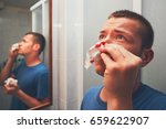 man with nose bleed in bathroom.... | Shutterstock . vector #659622907