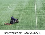 A Man Mowing The Grass On A...