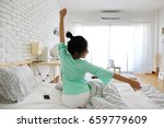 charming asian woman sit on bed ... | Shutterstock . vector #659779609