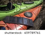 Small photo of Portable solar panels lie on an orange kayak and accumulate energy.