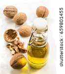 Small photo of walnut oil in a bottle on bright marble