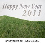 happy new year on sand & green grass background - stock photo
