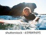 man lying on surfboard in the... | Shutterstock . vector #659849695