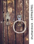 Small photo of Old vintage doork nock. Wooden aged door with keyhole and shabby metal door handles in the form of ring.