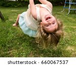 young girl swinging upside down ... | Shutterstock . vector #660067537