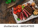 sliced rare grilled steak on... | Shutterstock . vector #660147505