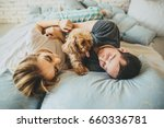 Stock photo top view of happy young family relaxing on bed together man and woman with pet dog in bedroom 660336781