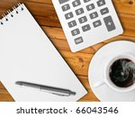 White calculator and white note paper with pen and white cup of hot coffee on wood table - stock photo