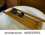 Small photo of Wooden bathtub tray with bath accouterments.