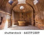 Small photo of The interior of main public baths in ruins of Ancient Roman city Pompeii, Campania region, Italy. Sunny day. City destroyed by the eruption of Mount Vesuvius. Inside of Forum Baths. Big bowl for water
